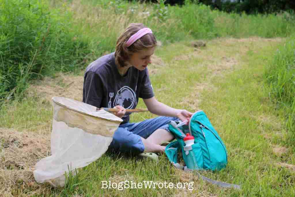 teen girl collecting insects in the grass