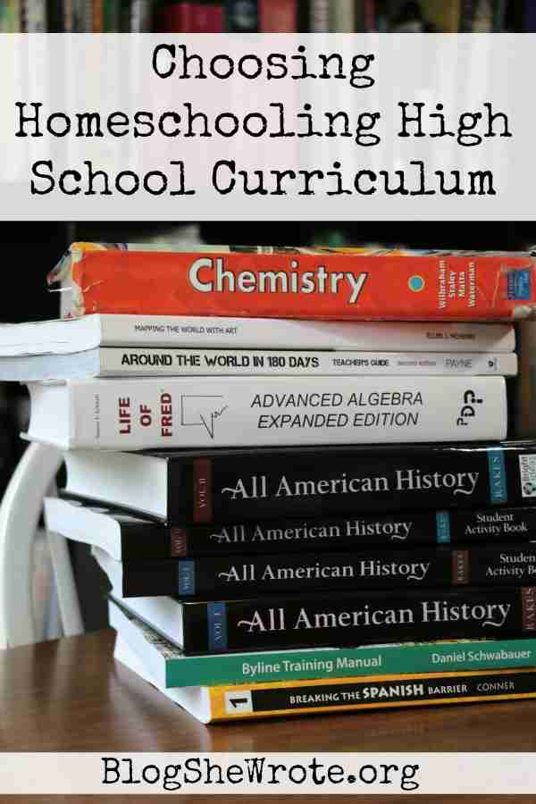 Stack of textbooks on a table in front of a bookshelf
