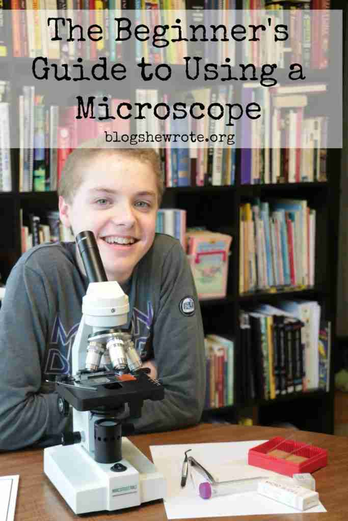 teen boy smiling behind a microscope