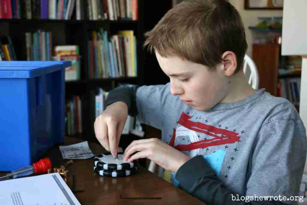 How to Homeschool High School Your Way 3- 9th grader putting together the wheel of a Tetrix robot