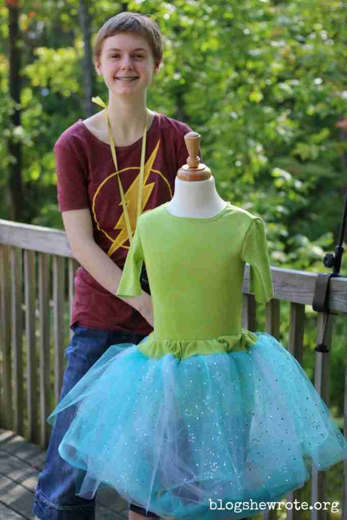 Homeschooling High School Your Way 2- a teen standing next to a child sized dress form modeling a piece from her fashion portfolio