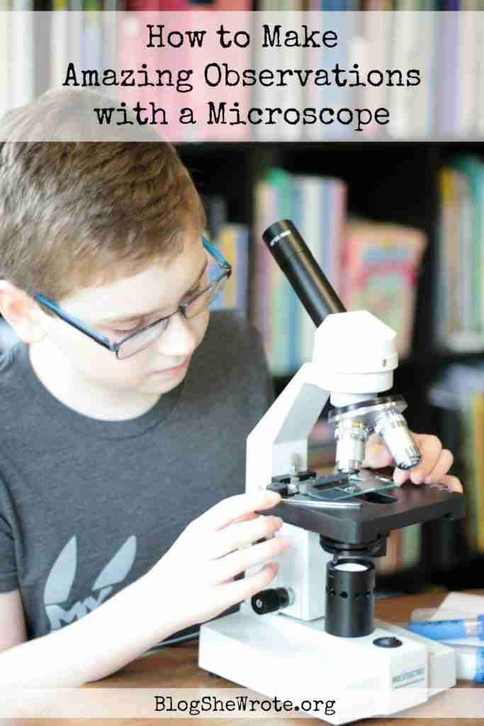 middle school boy placing a slide under a microscope