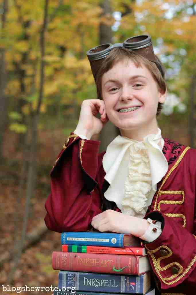 teen girl in a pirate costume she made with a stack of books in her lap