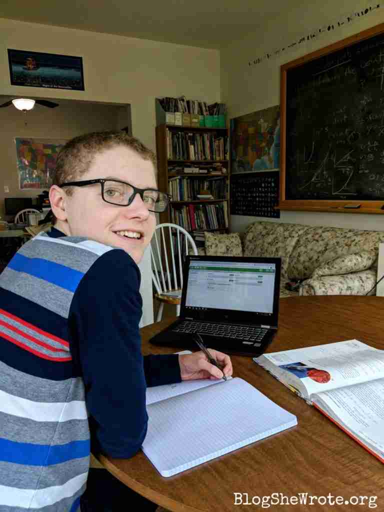 teen boy smiling at his work at a laptop