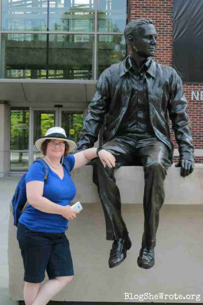 woman standing next to a statue of Neil Armstrong