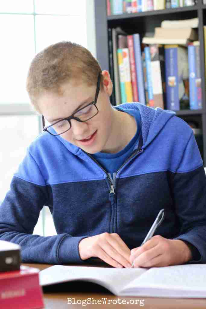 Are You Ready to Homeschool High School with Peace and Confidence- a teen boy writing in a notebook