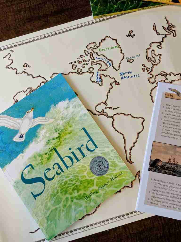 a map with a storybook and a literature guide on top