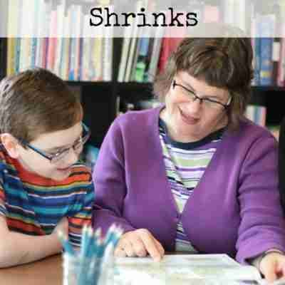 mom and a teen boy look over an atlas together at a table