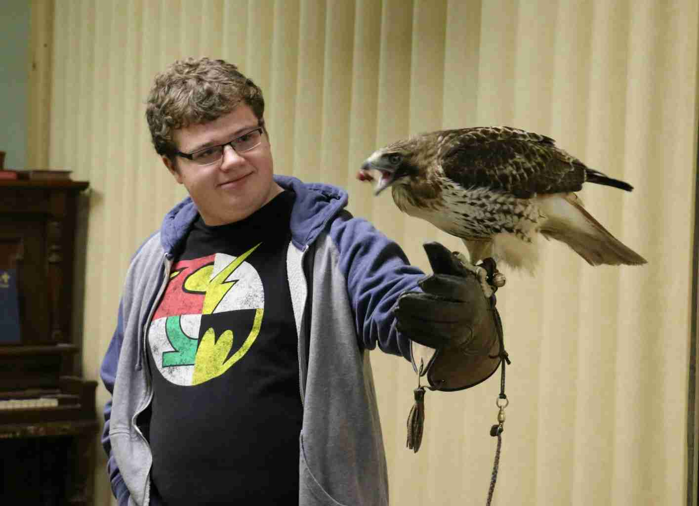 Homeschooling High School by Design- a teenage boy holding a red tail hawk with a falconer's glove