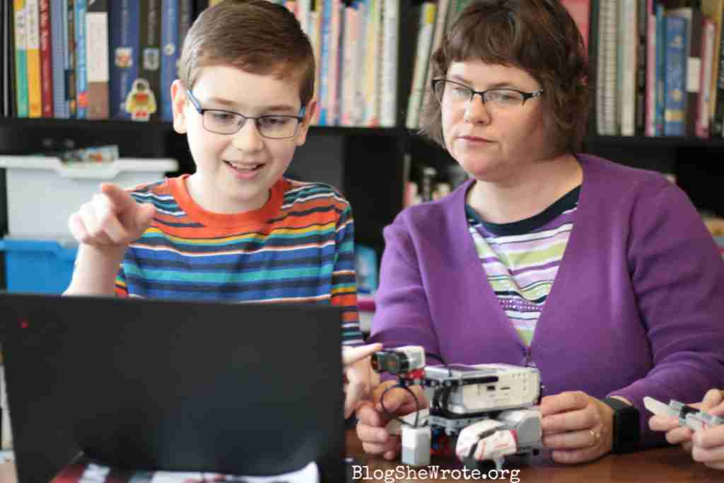 High School Teachers Are on a Special Journey Too- me working with a teen boy on a robotics problem sitting at a laptop with a Mindstorms robot