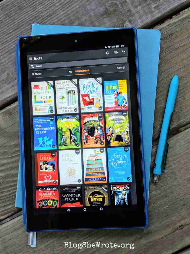 Kindle library display on a 10 inch Kindle Fire with a notebook and pen underneath and nearby