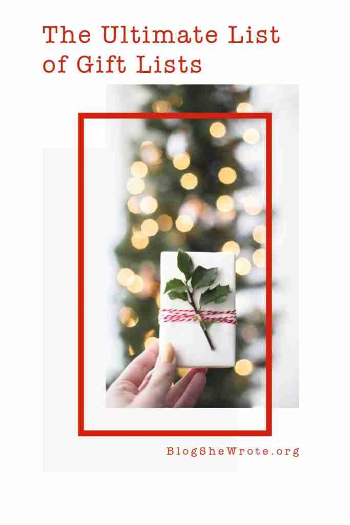 a woman's hand holding up a gift in front of a holiday tree