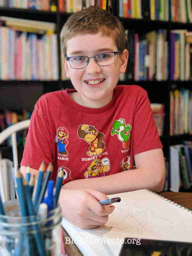 boy holding sketching pencils with a smile