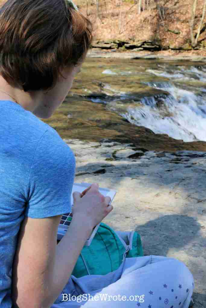 How to Avoid 7 Common Pitfalls of Homeschooling High School Planning- teen girl at a creek doing art