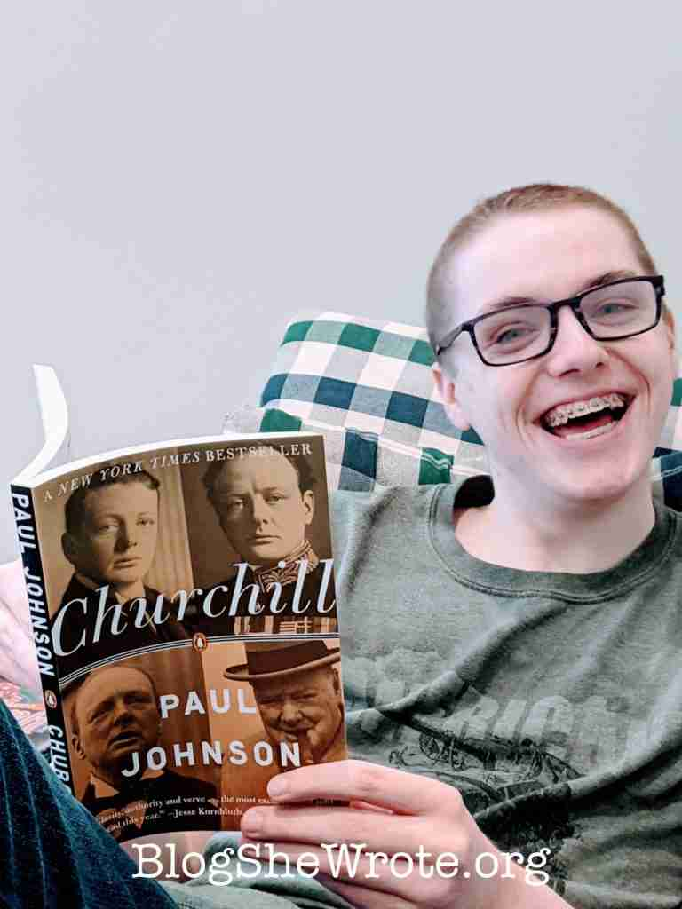 high school senior holding a Churchill book with a smile