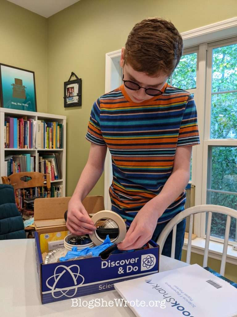 teen boy looking through a box of science goodies