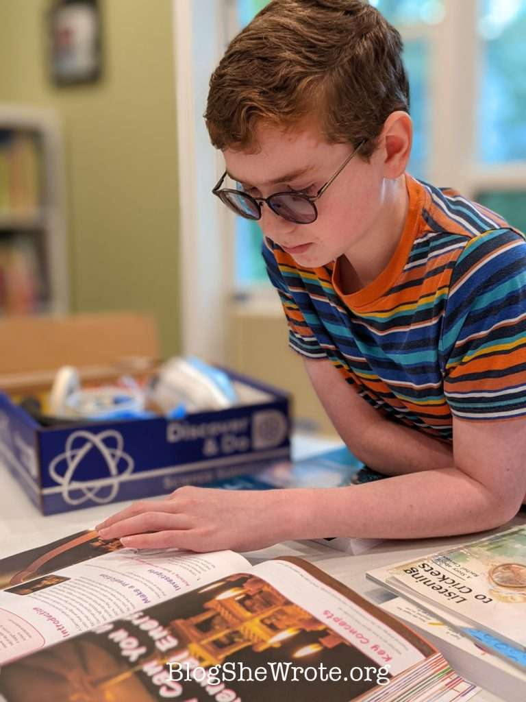 teen boy leaning over a lab manual reading next to a box of science materials