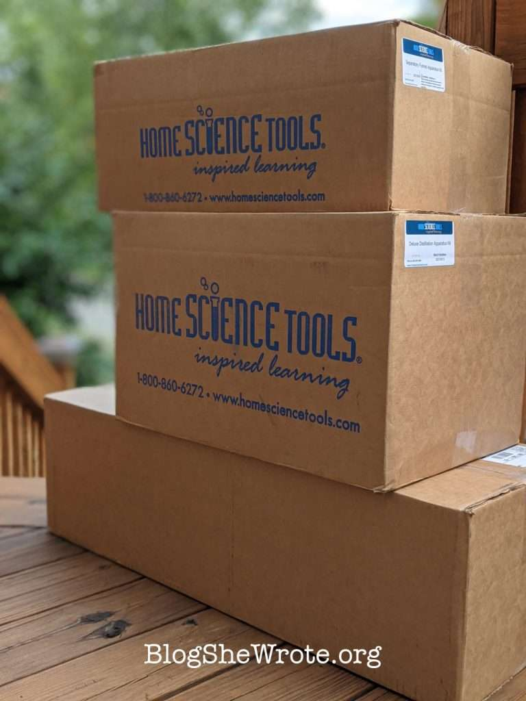 a stack of three large boxes on a porch with Home Science Tools in the side