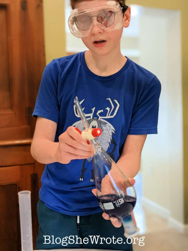 a teen boy venting a separatory funnel with blue liquid inside